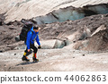 A mountaineer with a backpack walks in crampons walking along a dusty glacier with sidewalks in the 44062863