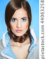 Beautiful young girl in a blue fur coat with a white collar with bright make-up and blue eyes 44063258
