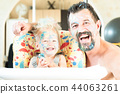 Father and little son are laughing. The faces and hair are stained with multicolored paints. Happy 44063261