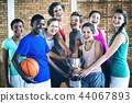 Smiling high school kids holding trophy in basketball court 44067893
