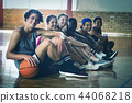 High school kids sitting on the floor in basketball court indoors 44068218