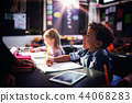 Teacher interacting with schoolboy in classroom 44068283