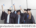 Composite image of portrait of smiling students holding degree 44068536