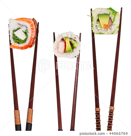 Traditional japanese sushi pieces placed between chopsticks, separated on white background. 44068769