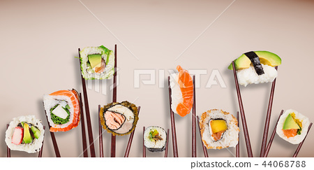 Traditional japanese sushi pieces placed between chopsticks on pastel color background. 44068788