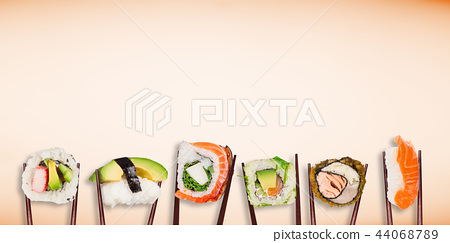 Traditional japanese sushi pieces placed between chopsticks on pastel color background. 44068789