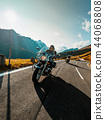 Motorcycle driver riding japanese high power cruiser in Alpine highway on famous Hochalpenstrasse, Austria. 44068808