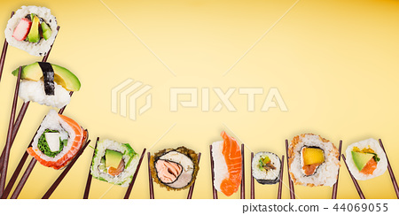 Traditional japanese sushi pieces placed between chopsticks on pastel color background. 44069055