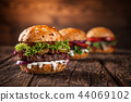 Tasty burgers on wooden table. 44069102