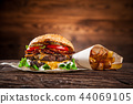 Tasty burgers on wooden table. 44069105