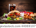 Tasty burgers on wooden table. 44069107