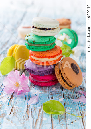 Colorful tasty macaroons on old wooden table. 44069116