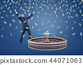 A businessman stands near a casino roulette and under rain of money bills. 44071063
