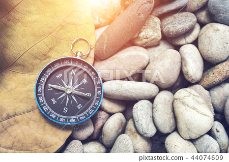 Navigation compass on old leaf and stone pebbles 44074609