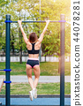 Woman pull-ups herself up on bar on sports ground in park. 44078281