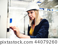 A portrait of an industrial woman engineer in a factory checking something. 44079260