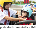 Mother attaching daughters  helmet on go kart  44079369