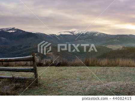 wooden fence on meadow with frozen grass 44082415