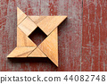 Tangram puzzle in shuriken shape on old wood 44082748