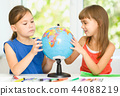 Little girls are examining globe 44088219