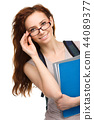 Young student girl is holding book 44089377