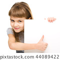 Little girl is looking out from the blank banner 44089422