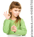 Happy little girl is showing OK sign 44089700