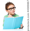 Young boy is daydreaming while reading book 44089867