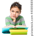 Young boy is daydreaming while reading book 44089889