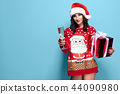 Pretty brunette woman in red pullover with Santa design, glass of champagne on blue background 44090980