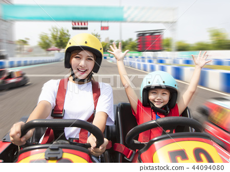 mother and daughter driving go kart on the track 44094080