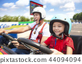 father and daughter driving go kart on the track 44094094
