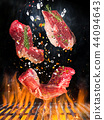 Raw beef steak on the grill with flames 44094643