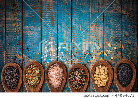Various spices in spoons on wooden table. 44094673