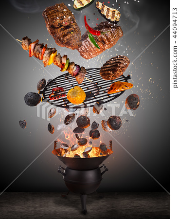 Kettle grill with hot briquettes, cast iron grate and tasty meats flying in the air. 44094713