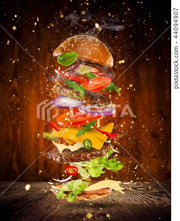 Big tasty burger with flying ingredients. 44094907