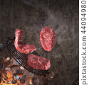 Kettle grill with hot briquettes, cast iron grate and tasty beef steaks flying in the air. 44094980