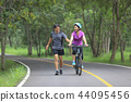 Middle aged couple walking with their bicycle 44095456