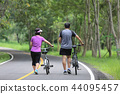 Middle aged couple walking with their bicycle  44095457