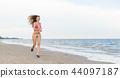 Attractive woman runs on sand beach in summer. 44097187