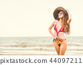 Happy young woman at beach in summer vacation. 44097211