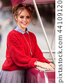 Portrait of pretty smiling curly redhaired girl is wearing red knitted sweater near stall with ice 44109120