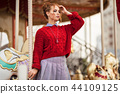 Portrait of pretty smiling curly redhaired girl is wearing red knitted sweater near carousel, autumn 44109125