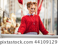 Portrait of pretty smiling curly redhaired girl is wearing red knitted sweater near carousel, autumn 44109129