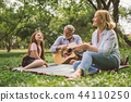 family playing guitar in their green park garden. 44110250