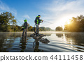 Fishermen holding fishing rod, standing in river 44111458