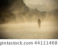 Fisherman holding fishing rod, standing in river 44111468