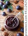 Plum jam in a glass jar. Fresh plum fruit  44112625