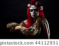 Monster woman with drawing face and flowers on head holding long snake piton in hands. 44112931