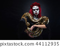 Monster girl with drawing face holding long snake piton in hands. 44112935
